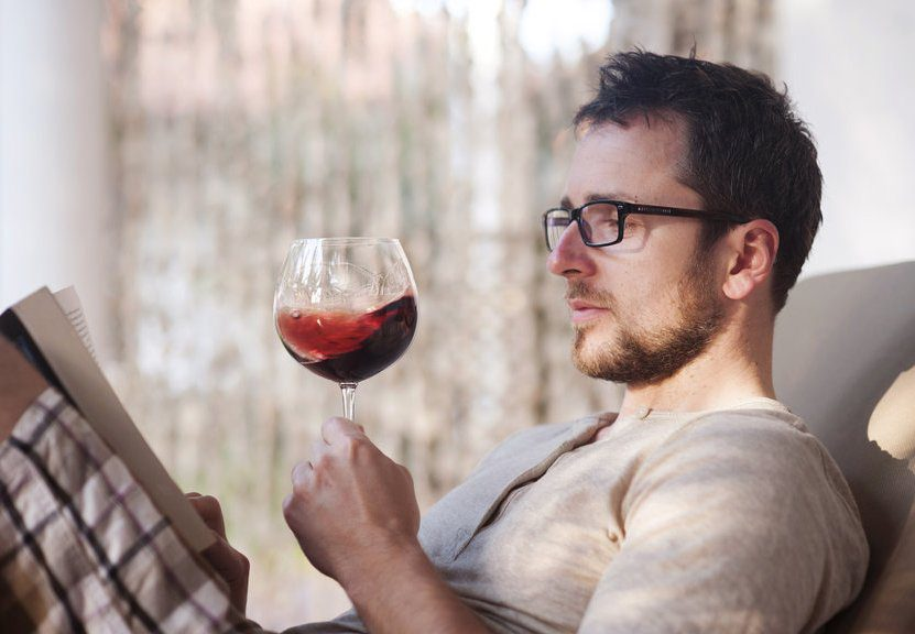 Man Reading Book while drinking a red wine